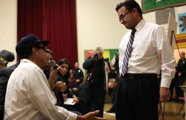 Refugio Nieto (left), father of deceased Alejandro, speaks with Supervisor David Campos.