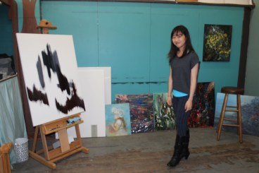 Sin stands next to some of her paintings inside her studio.