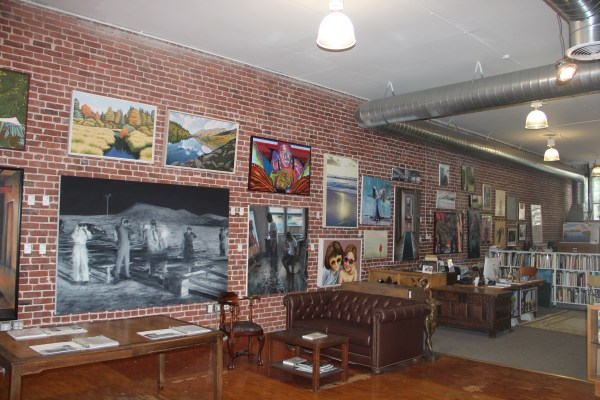 A variety of pieces, many by local artists, hang on an impressive brick wall. Photo by Joe Rivano Barros.