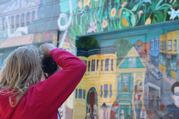 File photo by Leslie Nguyen-Okwu: A tourist snaps photos of Balmy Alley's famous murals.