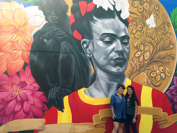 Muralists Elaine Chu and Marina Perez Wong in front of their mural-in-progress.