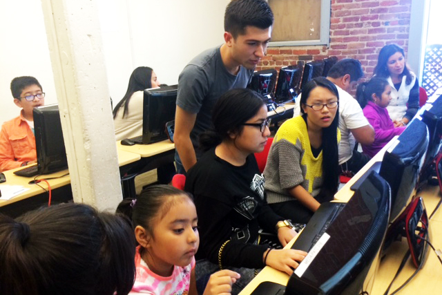 Former Google CS First fellow Dante Alvarado Leon instructs a group of children on coding. Photo by Laura Waxmann