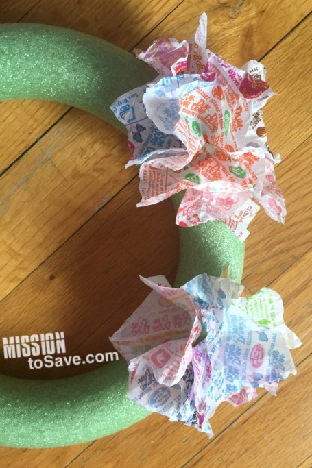 Looking for a clever and easy DIY decor project? This cuteDum Dums Wrapper Wreath is so sweet! See the tutorial for how to Make a Dum Dum Wrapper Wreath.