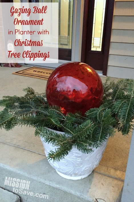 "If you get a live tree for the holiday, gather up those Christmas tree clippings! I love to use mine with gazing ball ""ornaments"" in my porch planters. See the post for more ways to use Christmas Tree clippings in your holiday decor. A frugal decorating tip!"