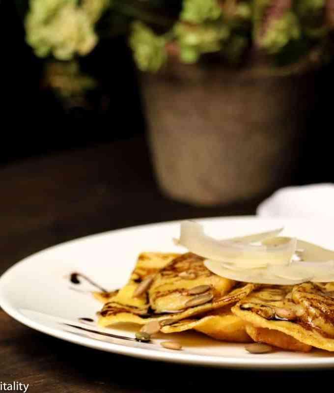 butternut squash ravioli with parmesan cheese, balsamic glaze, pumpkin seeds on a white plate