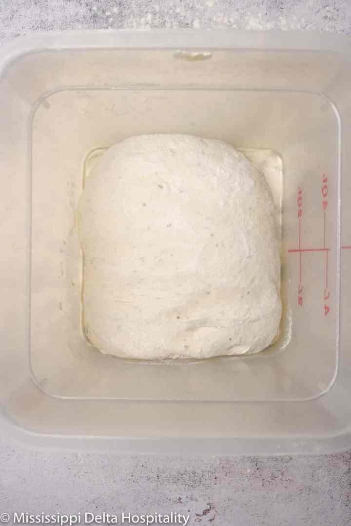 rosemary focaccia dough in a container after being folded