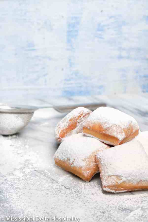 a pile of beignets on a marble board with a sieve and a blue background.