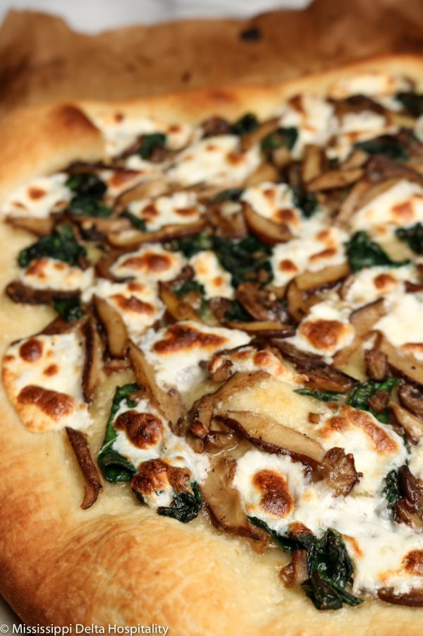 mushroom and spinach pizza on a piece of parchment paper