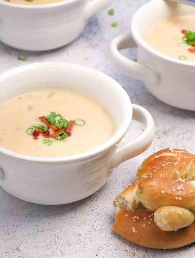 Three white farmhouse bowls of cheddar cheese soup with a pretzel on a concrete board