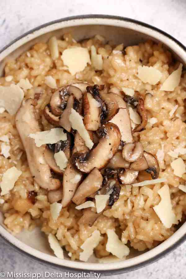 a bowl of mushroom risotto with parmesan shavings on top on a concrete board.