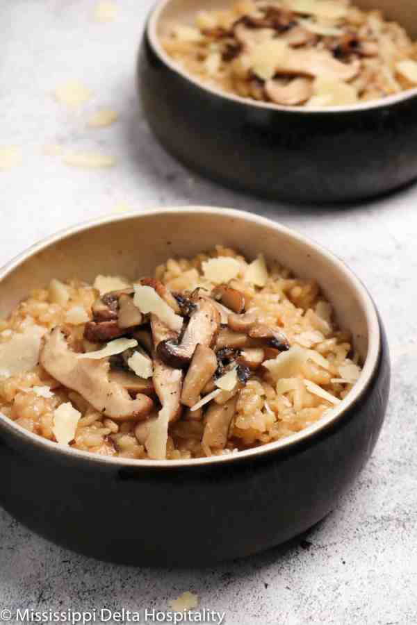 Two bowls of mushroom risotto with shaved parmesan on top.