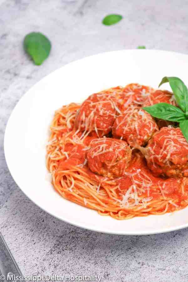 a bowl of spaghetti and meatballs with basil leaves on a concrete board.