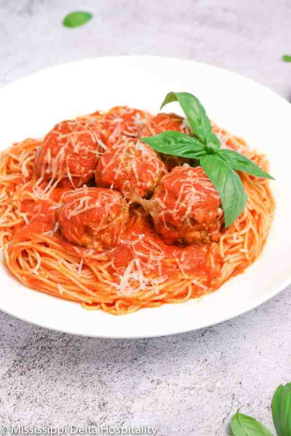 a bowl of spaghetti and meatballs with basil leaves and cheese on top on a concrete board.