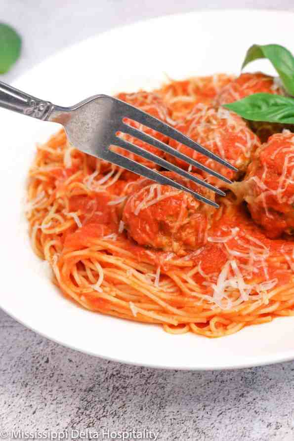 a bowl of spaghetti and meatballs with a fork in it on a concrete board.