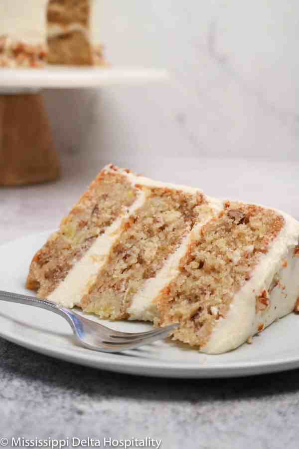 a slice of hummingbird cake on a light blue plate with a fork.