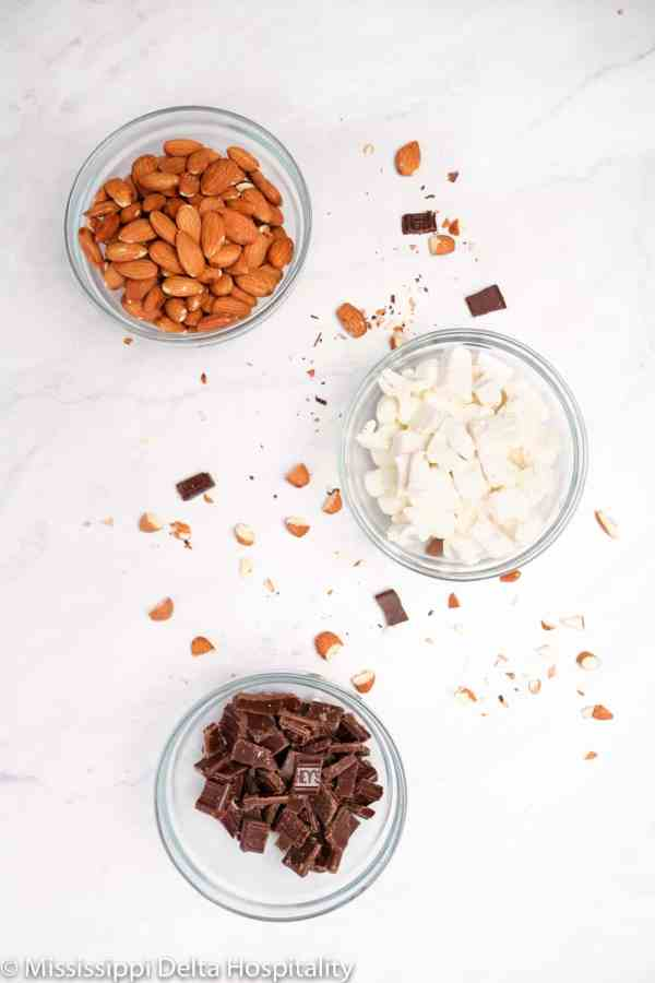 Three small glass bowls with marshmallows, chocolate chunks, and almonds in them.