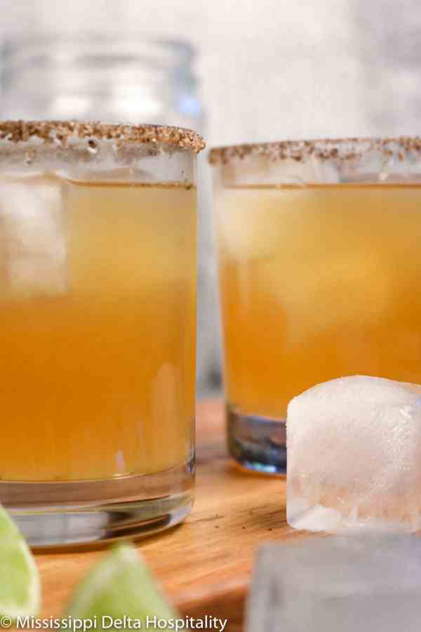 two glasses of margaritas on a wood board with two pieces of ice and two slices of lime.