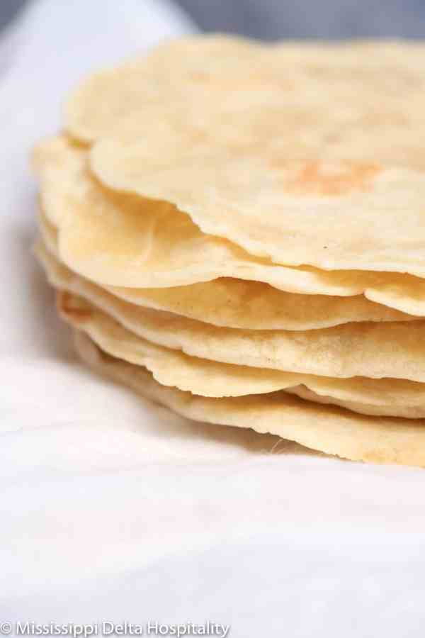seven tortillas on a white napkin.