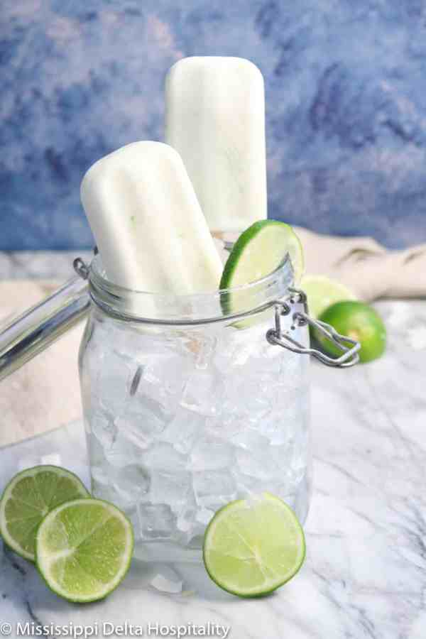 two coconut lime popsicles in a jar with ice and lime slices on a marble board with a blue background.