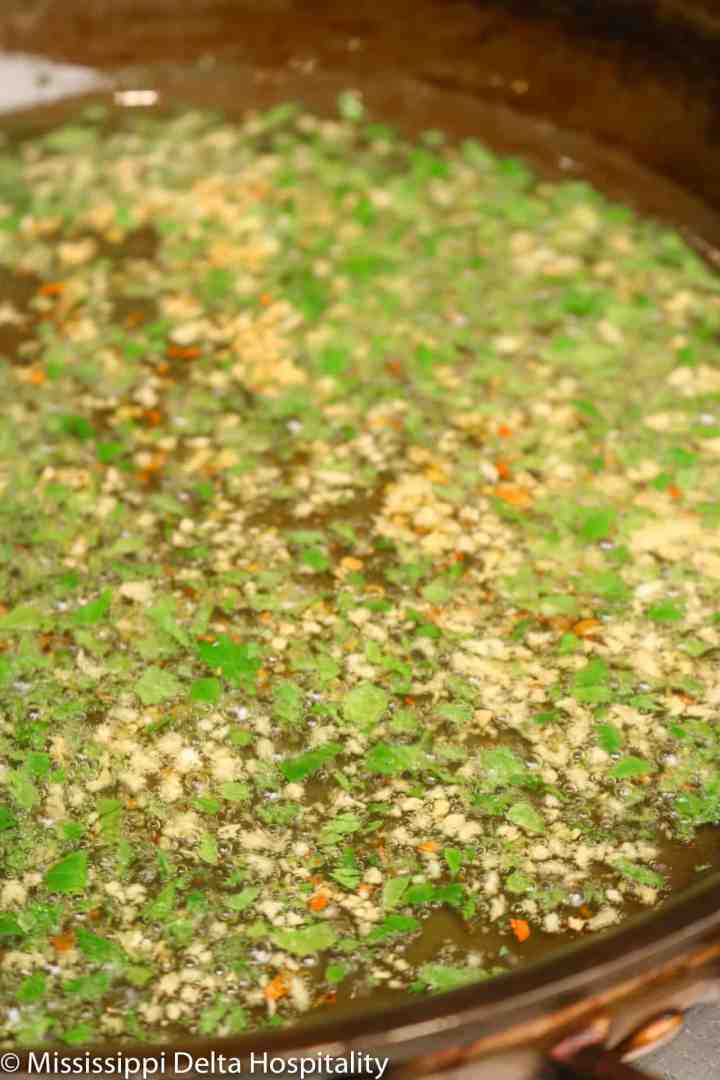 garlic, red pepper flakes, and parsley in a pan being cooked in oil