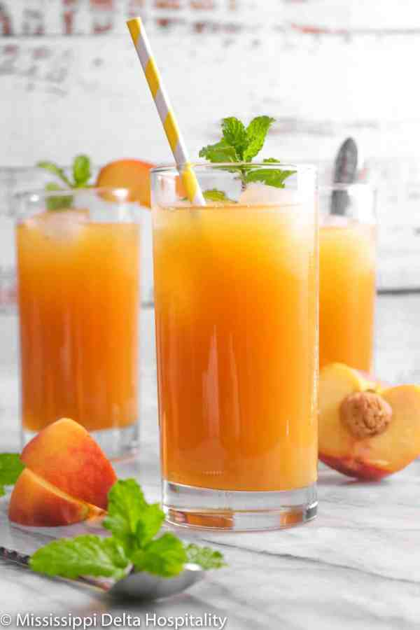 three glasses of peach iced tea with sliced peaches and mint sprigs