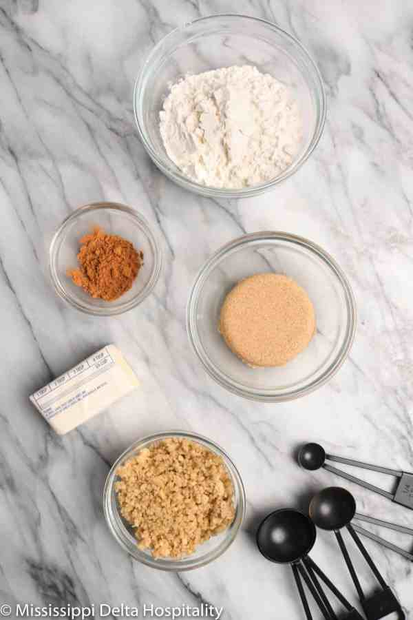 ingredients for apple crumble with measuring spoons on a marble board