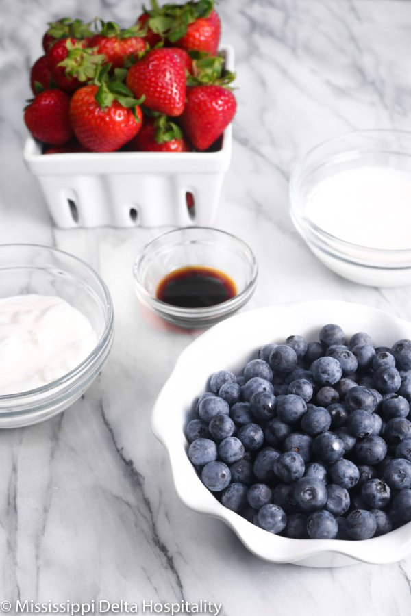 a bowl of blueberries, a basket of strawberries, and three bowls with heavy cream, vanilla, and sour cream on a marble board