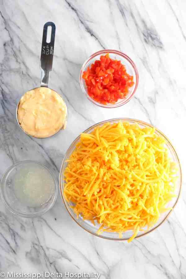 a bowl of grated cheddar cheese, chopped pimentos, a cup of mayo, and grated onion on a marble board