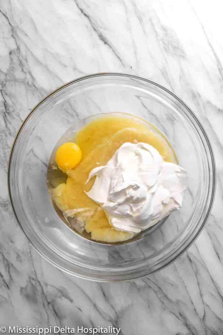 sour cream, an egg, apple sauce, and vegetable oil in a glass bowl