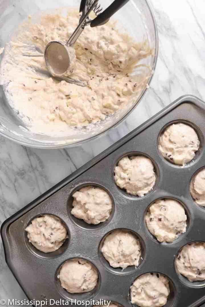 a muffin tin filled with batter and a glass bowl on a marble board