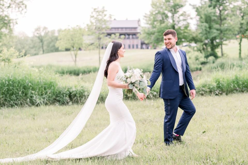 Bride and groom walking in a field in Iowa City, Iowa