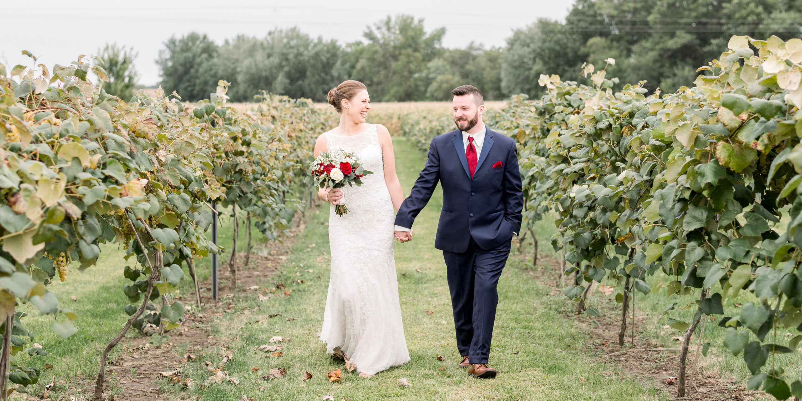 The bride and groom laughing as they walk through the vineyard at sunset at Tycoga Winery.