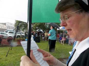 """Sister Judy intently hung onto her umbrella despite the pouring rain and driving wind as we sang """"This Alone""""."""