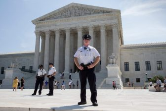 Officers stand watch over the plaza at the Supreme Court in Washington on Monday