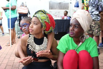 Right: Keyana Hawthorne looks on as dancers take the stage at Juneteenth Festival on Farish Street.