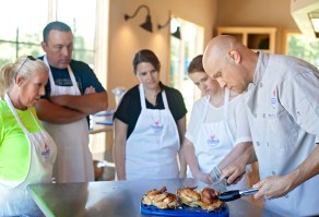 Cooking students, from left, Jennifer Ypya, Barry Ypya, Ann Marie McGee and Helen Ann Campbell watch as Executive Chef Matthew Sheeter cuts the lemon butter chicken prepared by the students Tuesday, June 7, at the Farmer's Table Cooking School in Livingston.