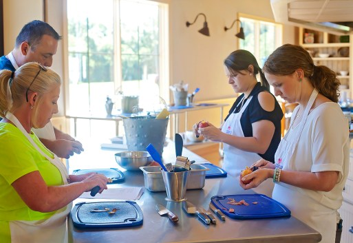 Cooking students, from left, Jennifer Ypya, Barry Ypya, Ann Marie McGee and Helen Ann Campbell peel peaches in preparation for their lesson on making peach galette Tuesday, June 7, at the Farmer's Table Cooking School in Livingston.