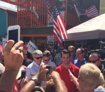 Gov. Phil Bryant, in sunglasses left, accompanies Donald Trump Jr., in red shirt, through the crowd of supporters at the Neshoba County Fair in July.