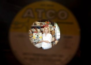 Little Big Store owner Betty Strachan is seen framed by one of the thousands of vinyl records sold in her store in Raymond. Strachan is celebrating 35 years in business.