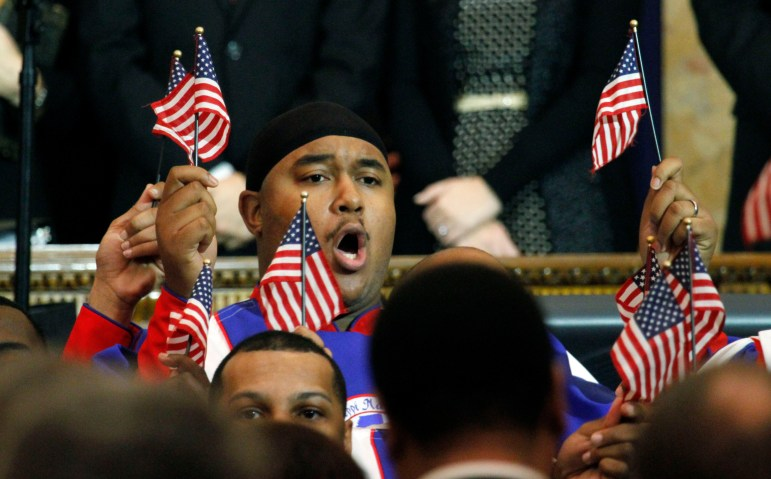 "A Mississippi Mass Choir member waves a small American flag during the group's rendition of ""America the Beautiful."" at the inauguration of Gov. Phil Bryant at the Capitol in Jackson on Jan 10, 2012."