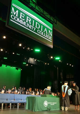 Meridian Community College President Scott Elliott presents a diploma to a student in May.