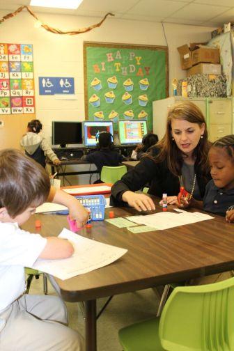 Jill Webb Hoda, assistant state literacy coordinator, works with children at Susie B. West Elementary School in Natchez-Adams School District.