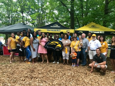 The Southern Miss Golden Eagles pose for a picture in front of their tent in Chastain Park.