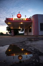 The iconic service station signage at Dockery Farms reflects in a sunset puddle.