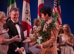Hyuma Kiyosawa is congratulated by USA IBC executive director Mona Nicholas and IBC Jury Chairman John Meehan for his men's junior silver medal win.