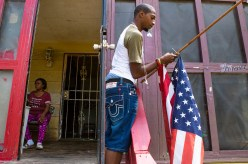Marilyn Martin, left, sits on her porch as her nephew, Lee Eric Evans, hangs a U.S. flag outside of Maritn's home on Davis Street in the Farish Street Historic District Tuesday, July 3, 2018.