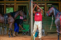 Antonio Ficklin, left, and Cedric Love prepare their horses for the harness racing competition at the Neshoba County Fair in Philadelphia, Miss. Tuesday, July 31, 2018.