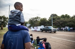 Cornelle Ransom holds holds his 3-year-old son, Cornelle Ransom Jr., on his shoulders as they watch Jackson State's homecoming parade near JSU's campus Saturday, October 13, 2018.
