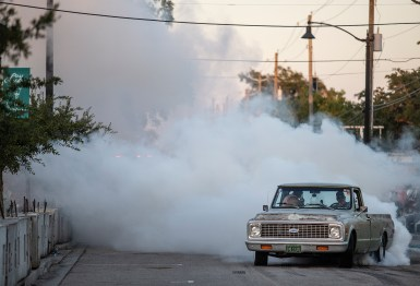 Tire smoke comes from a truck while performing a burnout in the Burn 'em Up in the Pass competition during the 22nd Annual Cruisin' The Coast event in Pass Christian Thursday, October 4, 2018.