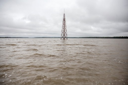 A radio tower surrounded by flood water near Mayersville Miss., Friday, April 5, 2019.